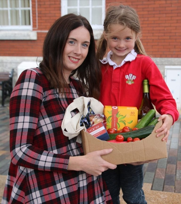 Image showing mother and young girl holding cardboard box of plastic free fruit and vegetables