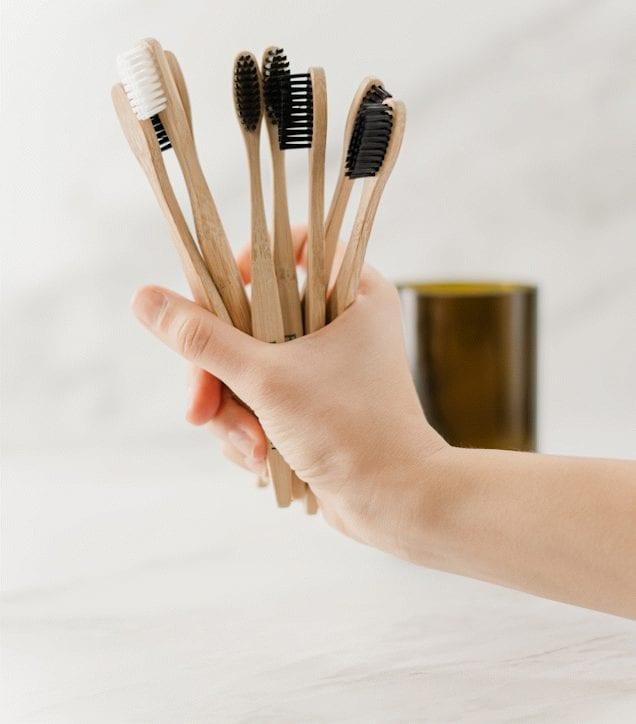 Image of woman's hand holding a selection of wooden toothbrushes