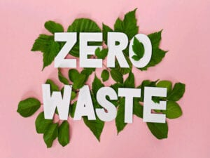 Words 'zero waste' in white caps on bed of green leaves against pink background