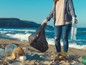 Woman picking up plastic waste on a beach