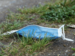 Discarded single use face mask lying on grass
