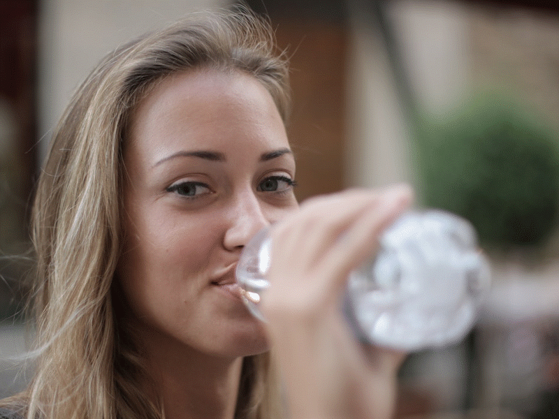 Young woman drinking from plastic bottle