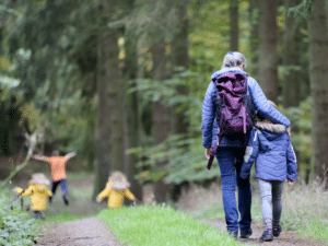 Woman and children walking in woodland.