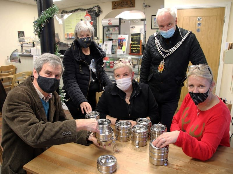 Five people, two standing and three seated, all wearing masks, showing off tiffin tins